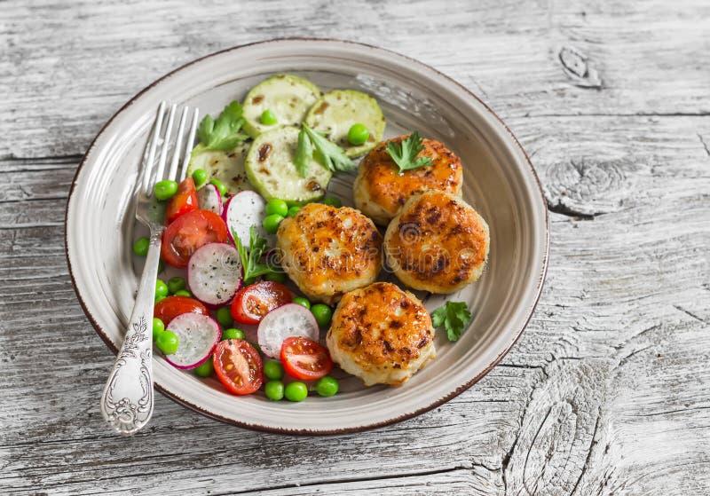 Kippenkoteletten, geroosterde courgette en verse groentesalade stock foto's