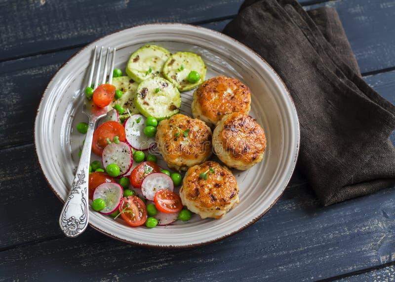 Kippenkoteletten, geroosterde courgette en verse groentesalade stock foto