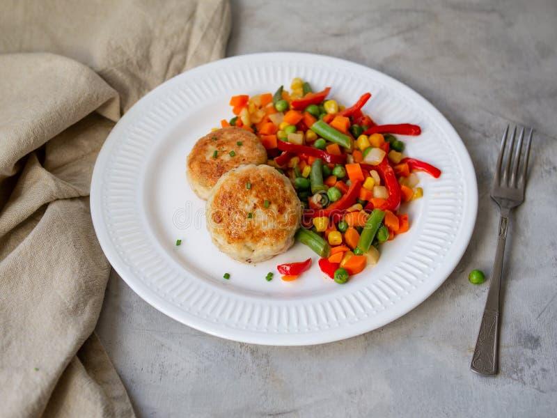 Kippenkoteletten met gestoomde Mengelingsgroenten, de ballen van het Kippenvlees op witte plaat Heathy lunch, dieetvoedsel De sel stock afbeeldingen