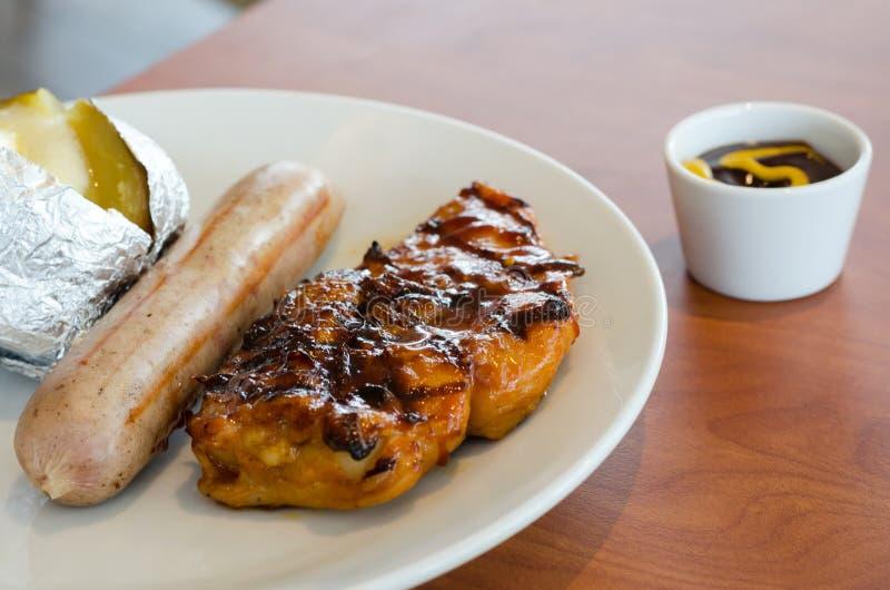 Kippenlapje vlees met varkensvleessuasage en brijaardappel royalty-vrije stock afbeeldingen