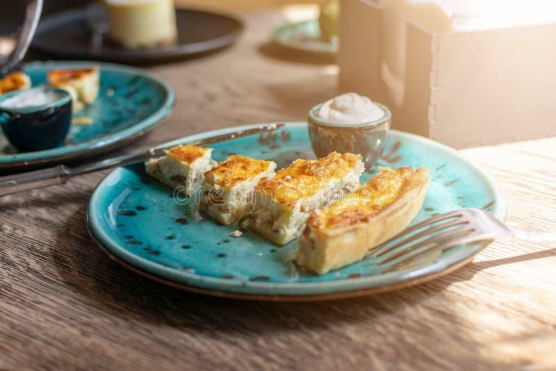 Kippenquiche met paddestoelenrecept Quiche Lotharingen met kip en Champignons en saus op een blauwe plaat op houten lijst pastei royalty-vrije stock afbeelding