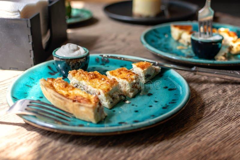 Kippenquiche met paddestoelenrecept Quiche Lotharingen met kip en Champignons en saus op een blauwe plaat op houten lijst pastei stock fotografie