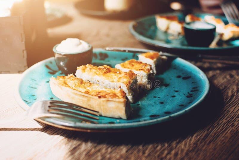 Kippenquiche met paddestoelenrecept Quiche Lotharingen met kip en Champignons en saus op een blauwe plaat op houten lijst pastei stock afbeelding
