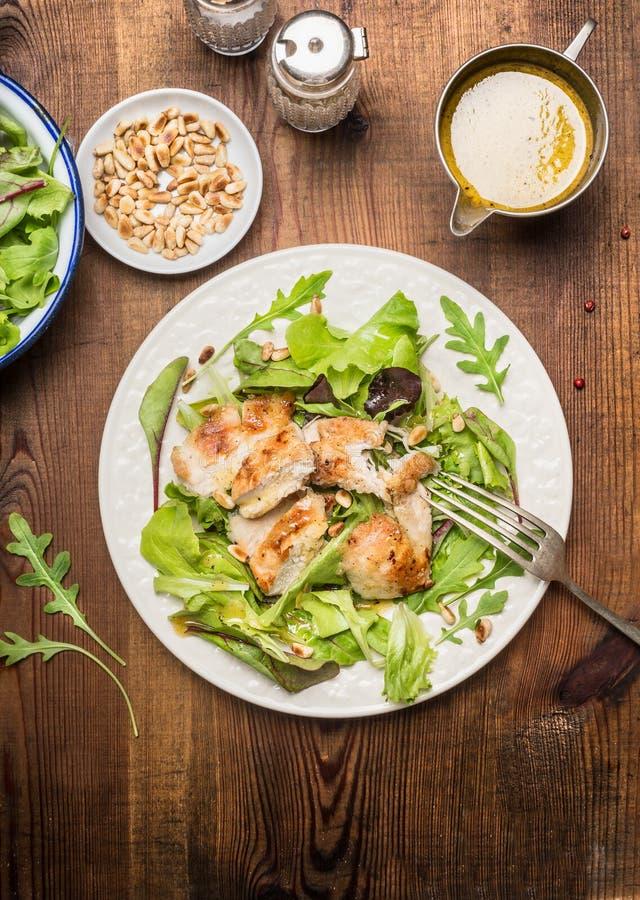 Kippensalade met groene saladebladeren, pijnboomnoten en olijfolievulling Gezonde voedingsalade op rustieke houten achtergrond, h stock foto's