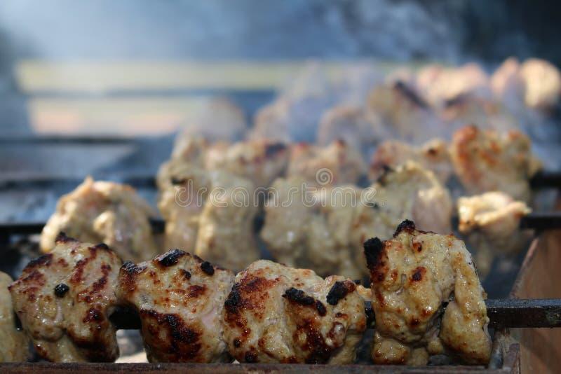 Kippentikka op skeweres over barbecuegrill royalty-vrije stock afbeelding
