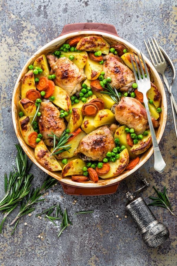 Kippenvlees, dijen met aardappel, wortel en groene erwten worden gebakken die royalty-vrije stock foto