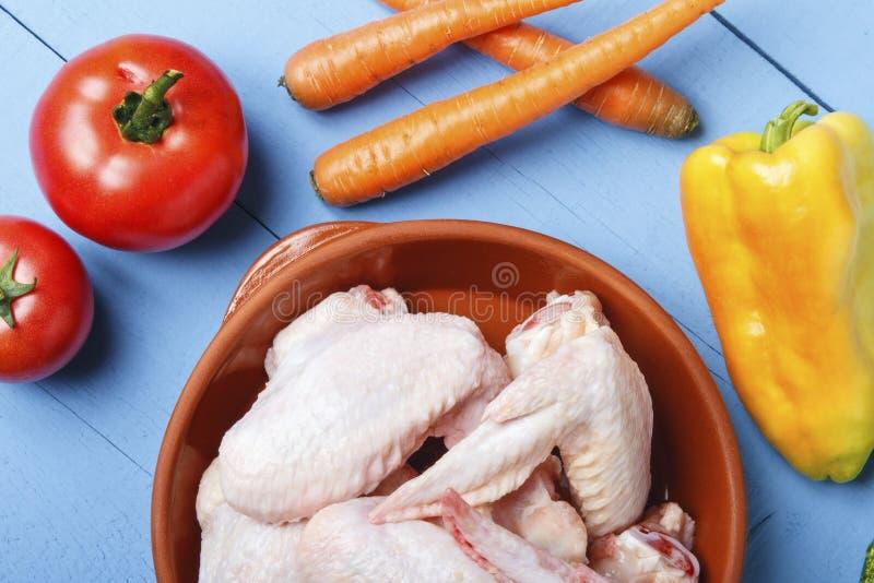 Kippenvleugels in ceramische waren en verse organische groenten op houten lijst Rode tomaten, wortel en gele groene paprika Hoogs stock afbeeldingen