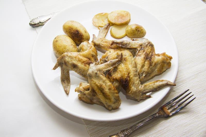 Kippenvleugels en aardappel in de schil royalty-vrije stock foto's