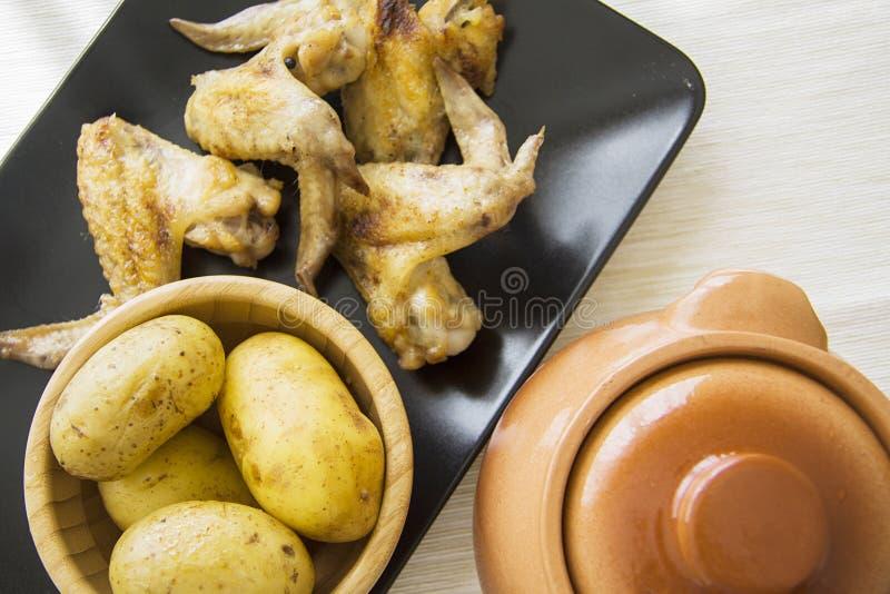 Kippenvleugels en aardappel met kleipot stock foto's