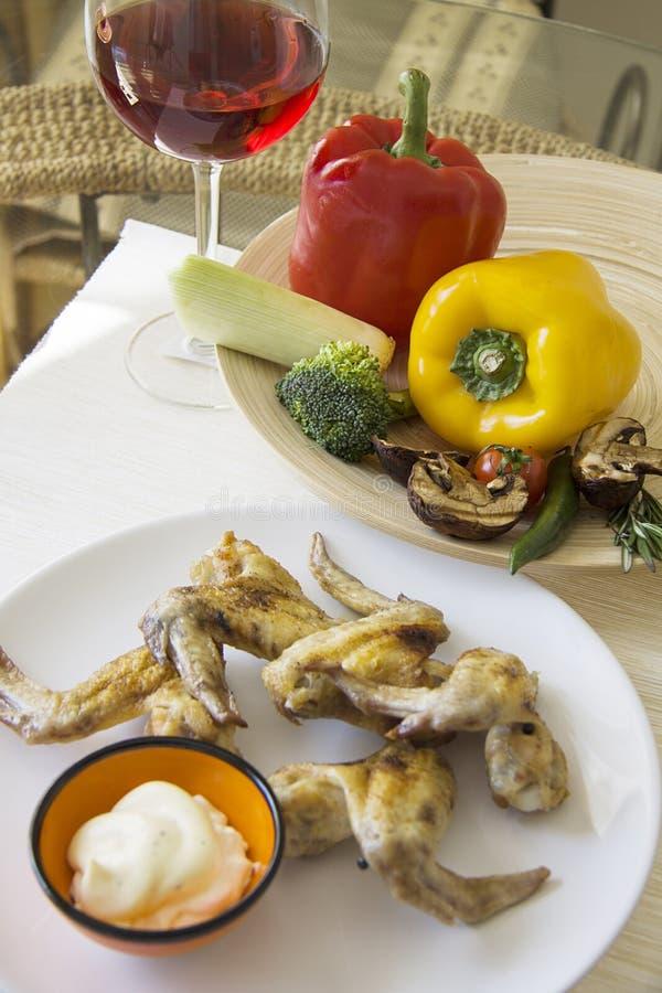 Kippenvleugels en plantaardige plaat met glas rode wijn stock afbeeldingen