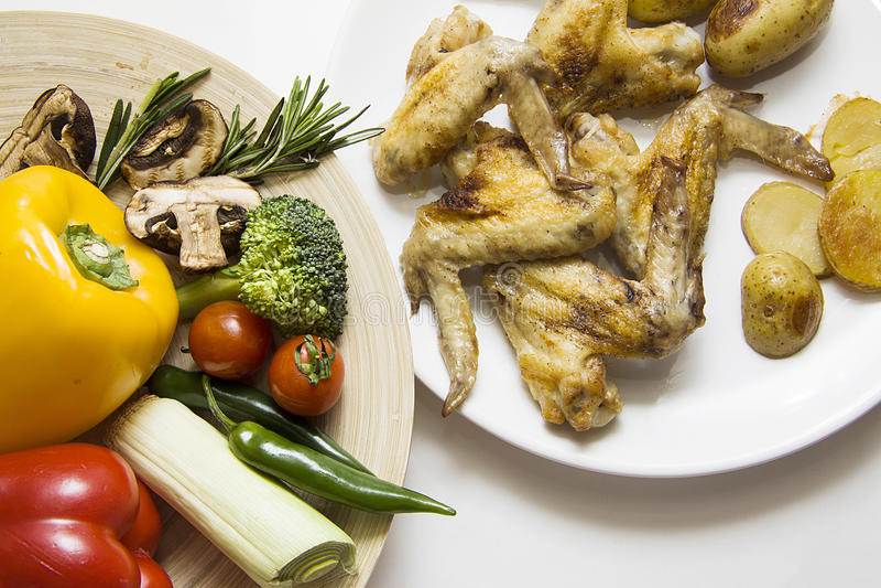 Kippenvleugels en plantaardige plaat op beige tafelkleed stock afbeelding