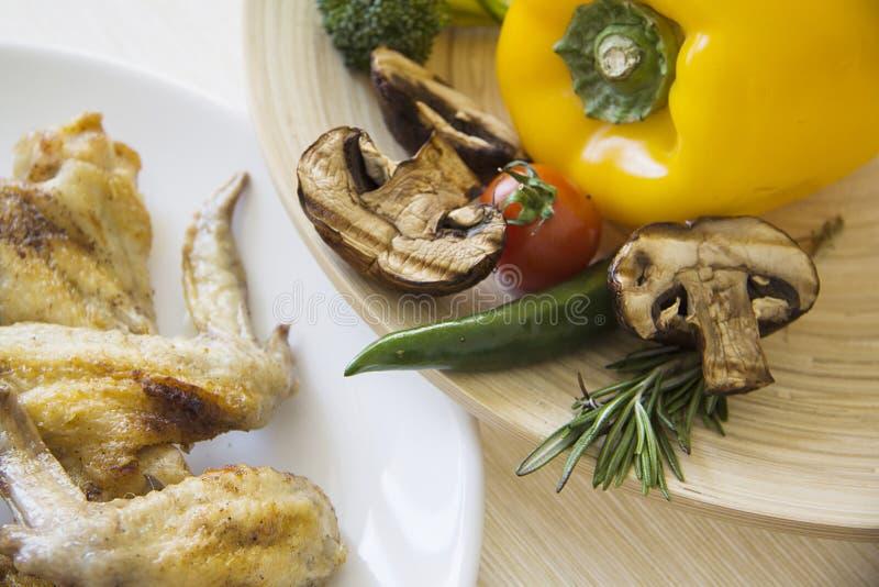 Kippenvleugels en plantaardige plaat op beige tafelkleed royalty-vrije stock afbeeldingen