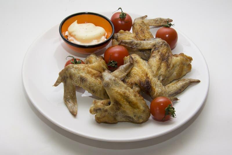 Kippenvleugels en tomaten stock afbeeldingen