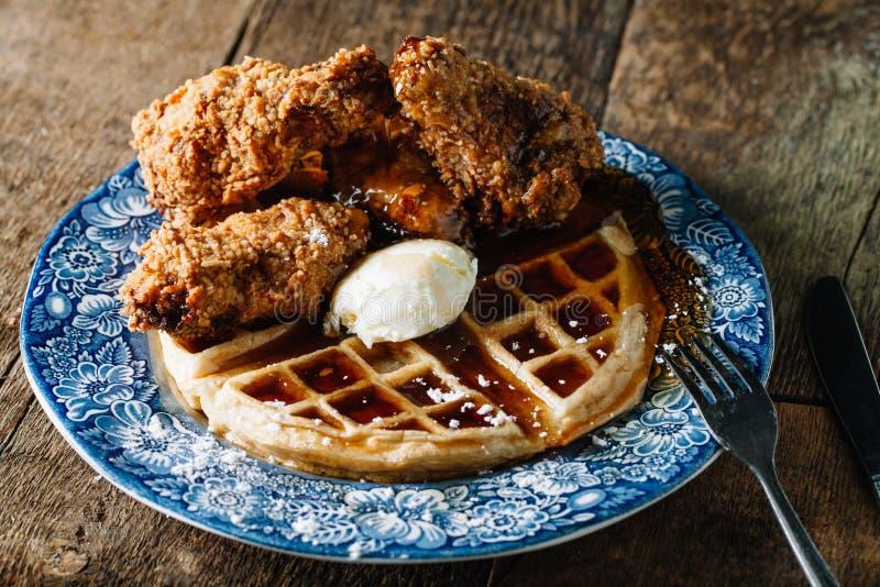 Kippenvleugels en wafels met boter en braambessensyru worden gediend die royalty-vrije stock foto