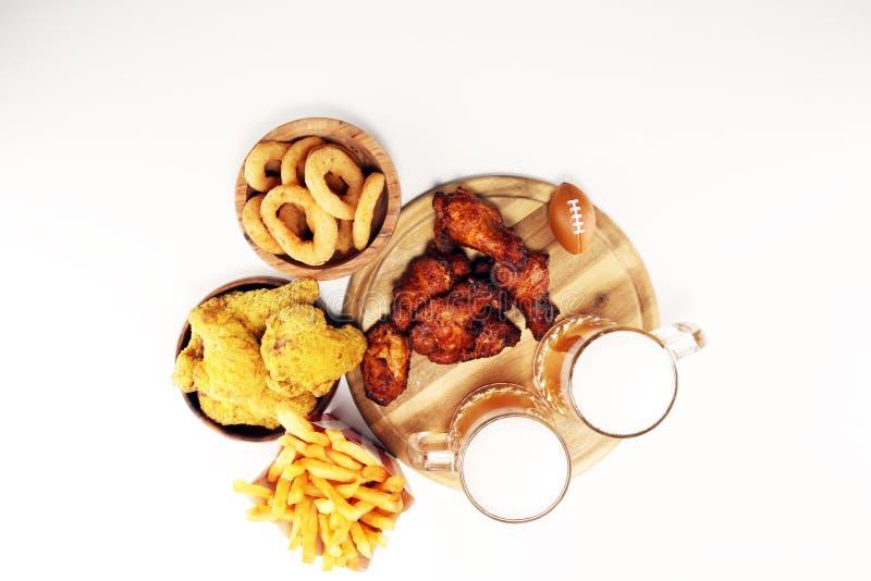 Kippenvleugels, gebraden gerechten en uiringen voor voetbal op een lijst Groot voor Komspel stock fotografie
