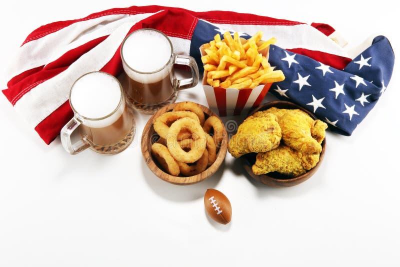 Kippenvleugels, gebraden gerechten en uiringen voor voetbal op een lijst Groot voor Komspel stock afbeelding