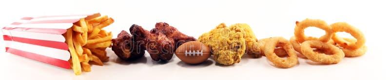 Kippenvleugels, gebraden gerechten en uiringen voor voetbal op een lijst Groot voor Komspel stock afbeeldingen