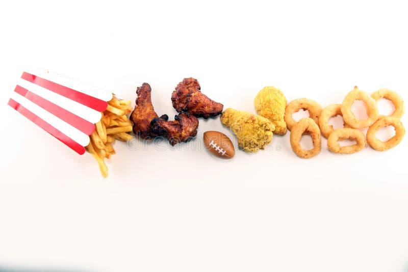 Kippenvleugels, gebraden gerechten en uiringen voor voetbal op een lijst Groot voor Komspel royalty-vrije stock foto