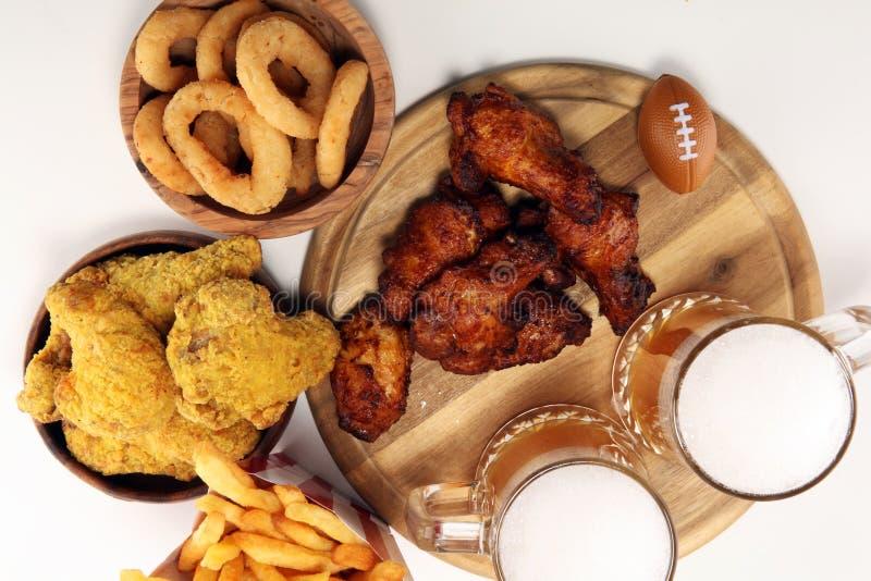 Kippenvleugels, gebraden gerechten en uiringen voor voetbal op een lijst Groot voor Komspel stock foto
