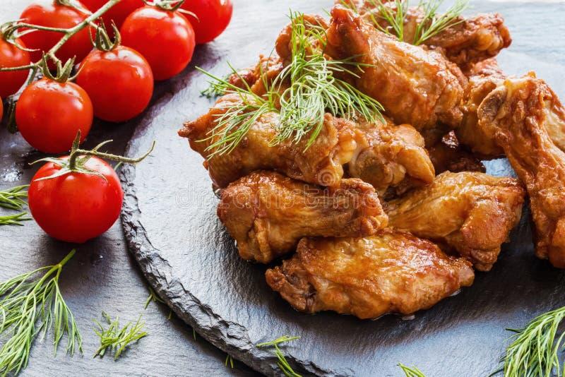 Kippenvleugels met barbecuesaus worden gekookt op zwarte steenachtergrond die Kleine kersentomaten en dille royalty-vrije stock foto's