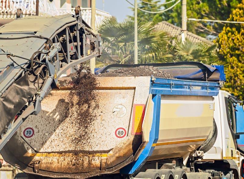 Kippersvrachtwagen in het werk van het asfalteren wordt gebruikt die Bouw Polen in stock foto