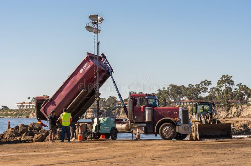 Kipplaster entlädt Schmutz auf Goleta-Strand, Kalifornien lizenzfreie stockfotos