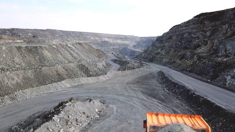 Kipplaster ist am Steinbruch Draufsicht des Fahrens des orange Kipplasters mit Schutt auf Straßentagebau Schwerer Transport im Be stockbilder