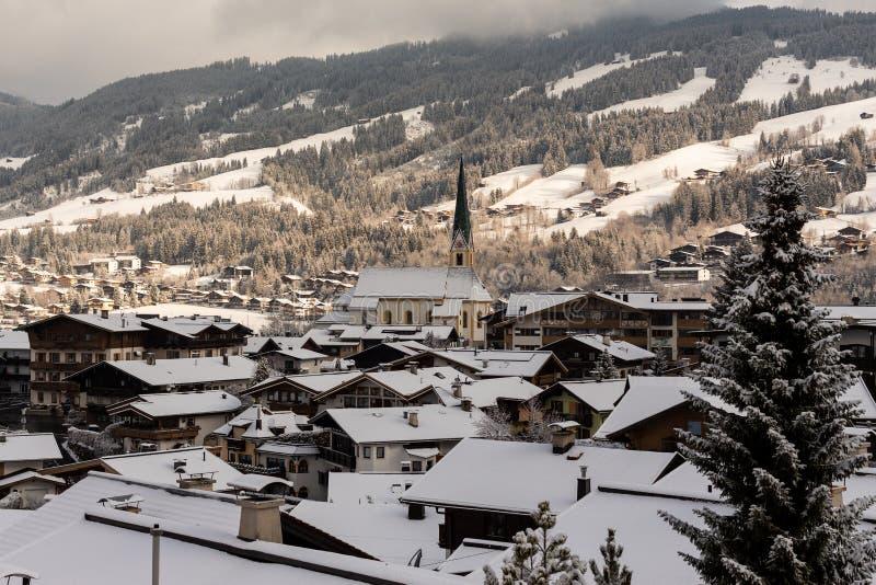 Kirchberg dans le Tirol, le Tirol/Autriche - 26 mars 2019 : Église et maisons dans le village couvert de couche de bidon de neig images libres de droits