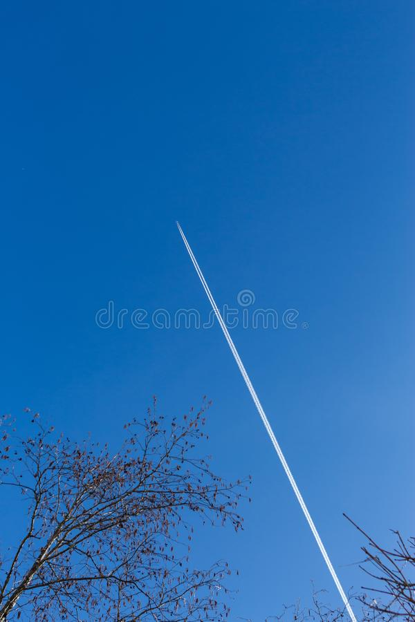 Kirchberg em Tirol, Tirol/Áustria - 24 de março de 2019: Céu azul profundo com um avião na alta altitude que deixa fugas imagem de stock