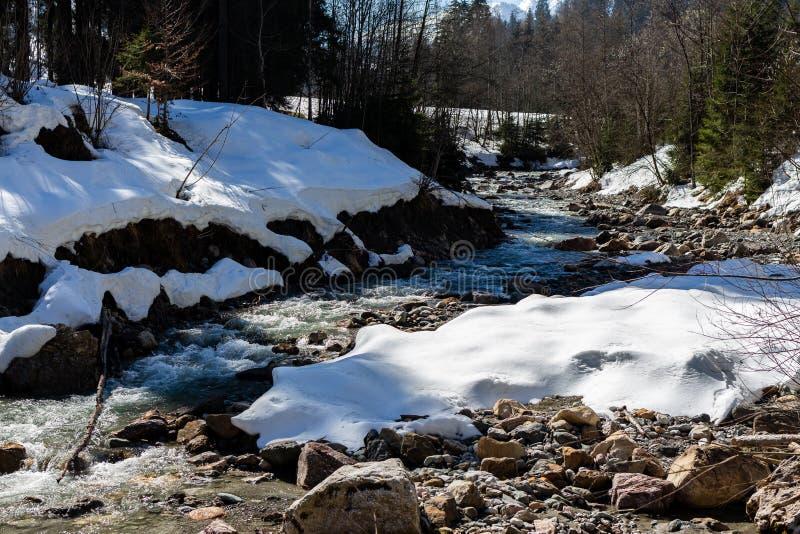 Kirchberg em Tirol, Tirol/Áustria - 24 de março de 2019: Neve e rio das rochas que correm através dos cumes austríacos imagens de stock royalty free