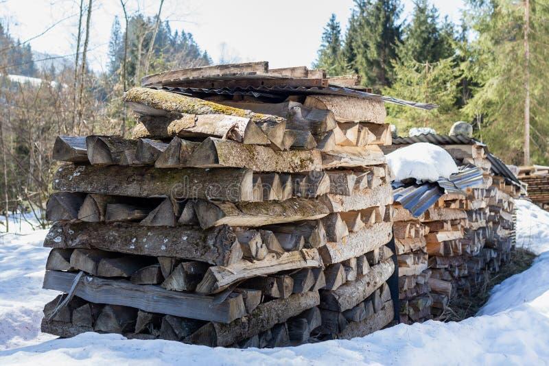 Kirchberg em Tirol, Tirol/Áustria - 24 de março de 2019: Pilhas da parte externa de madeira do fogo na neve fotos de stock