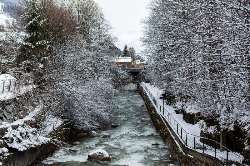 Kirchberg em Tirol, Tirol/Áustria - 26 de março de 2019: Rio que corre através da vila e de sua paisagem do inverno foto de stock