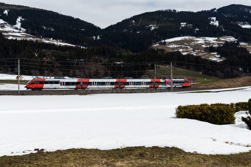 Kirchberg em Tirol, Tirol/Áustria: 28 de março de 2019: Trem do transporte público de OBB que conduz através do vale nevado imagem de stock royalty free