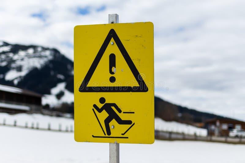 Kirchberg i Tirol, Tirol/Österrike: Mars 28 2019: det varnande tecknet, som varnar för folk på himlar, kunde korsa vägen här arkivbilder