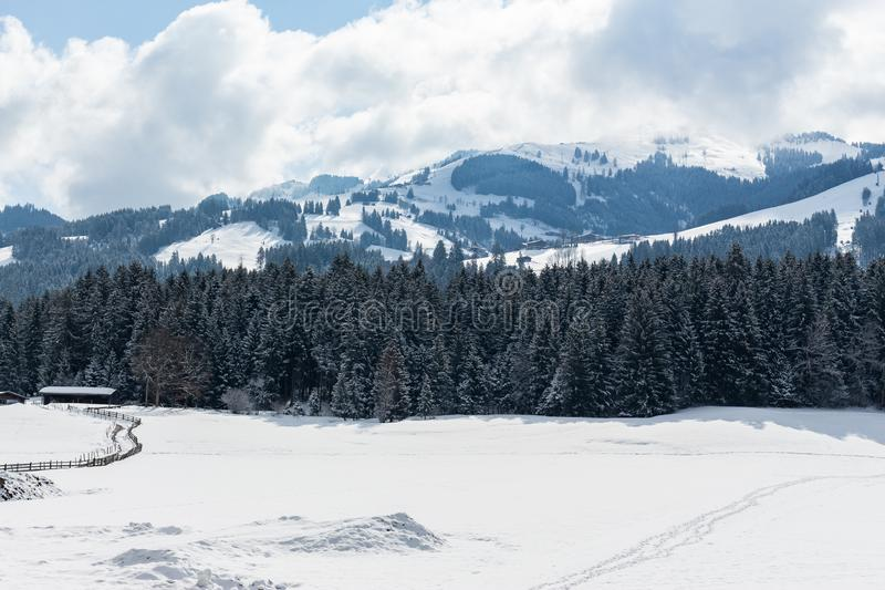 Kirchberg in Tirol, Tirol/Austria - March 26 2019: Austrian Alps landscape with snow covered mountains. As captured during a hike in the valley below royalty free stock image