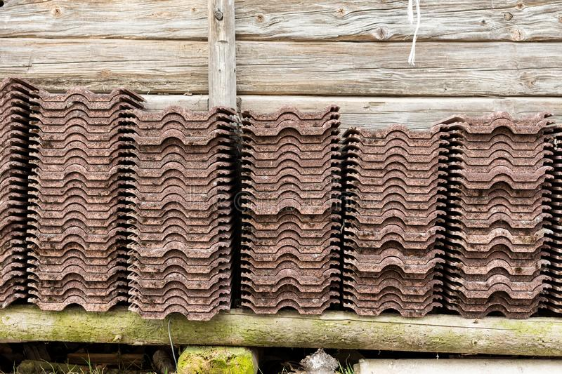 Kirchberg in Tirol, Tirol/Austria: March 28 2019: Big stacks of roof tiles against a wooden shed. Kirchberg in Tirol, Tirol/Austria: March 28 2019: Big stacks of royalty free stock image