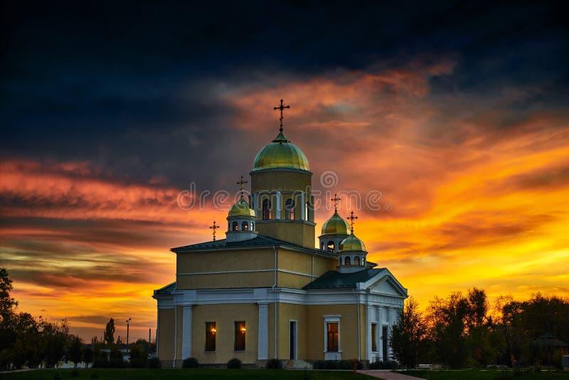 Kirche am Abend, am schönen bewölkten Himmel und an den Wolken bei Sonnenuntergang stockfotografie
