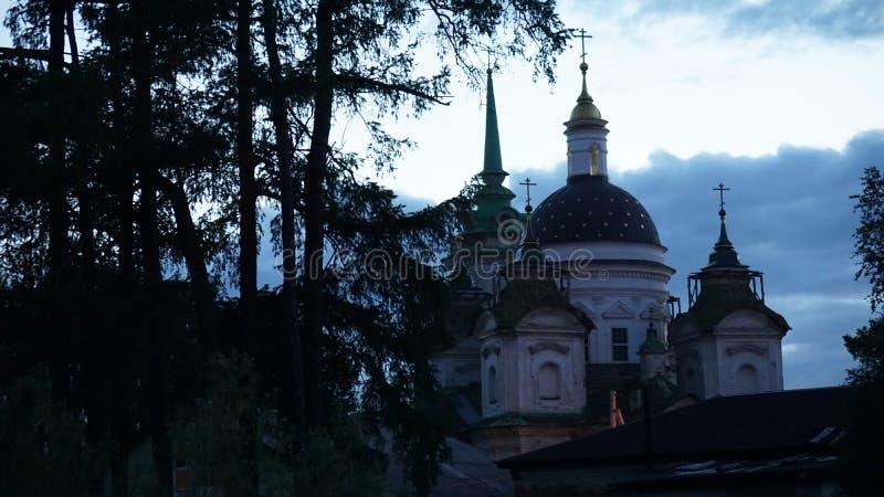 Kirche auf dem Hintergrund der dunklen Wolken des Sonnenuntergangs der Himmelbäume in Russland lizenzfreies stockfoto