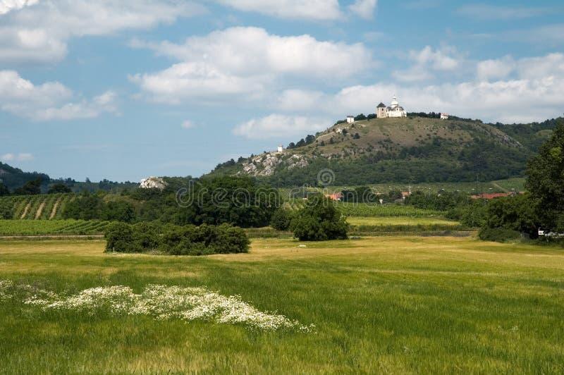 Kirche auf Hügel über Dorffeldszene lizenzfreie stockbilder