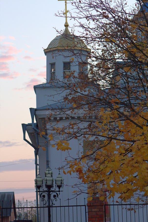 Kirche am Herbstabend, Kreuz, Blätter, Himmel, Architektur lizenzfreies stockbild