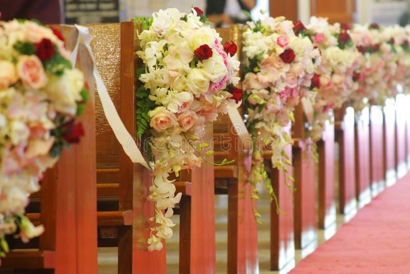 Kirchebänke verziert mit Blumensträußen stockfotografie