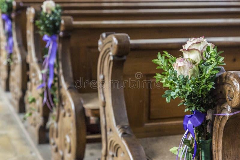 Kirchenbankdetails mit Blumenhochzeitsdekoration stockfotos