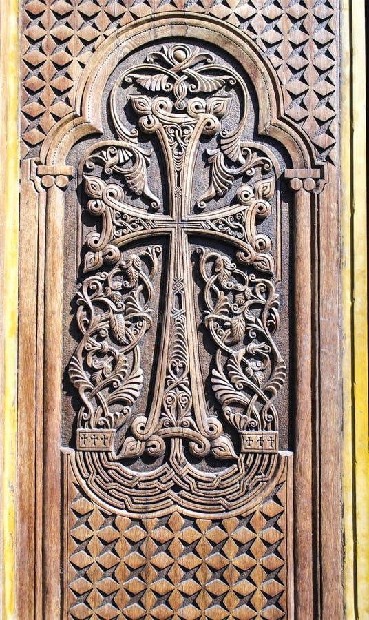 Kirchenholztür mit geschnitztem Kreuz baute vom Volksblumenmuster zusammen stockfotos