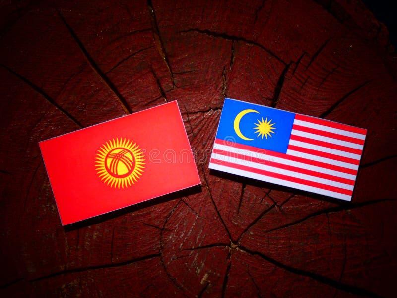 Kirgizistanflagga med den malaysiska flaggan på en isolerad trädstubbe vektor illustrationer