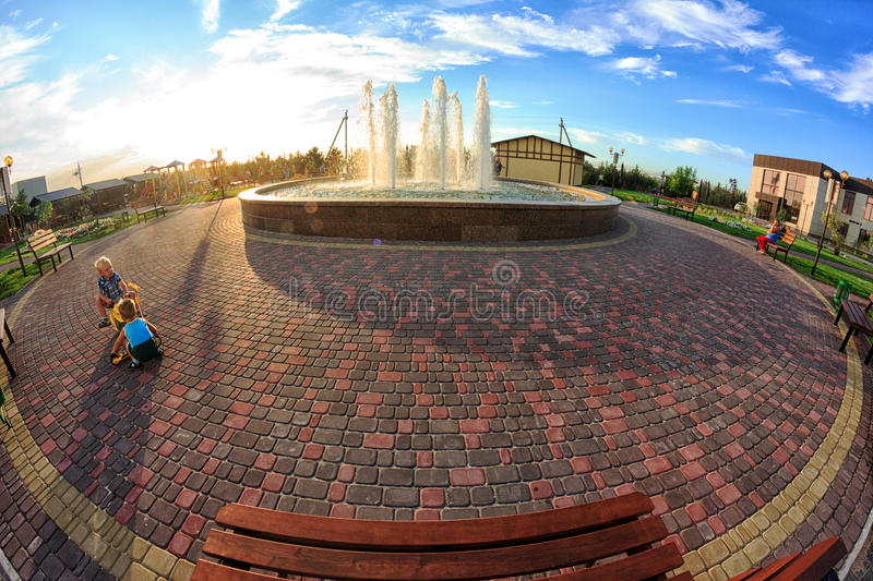 Kirillovka, Ukraine - August 28, 2016: Beautiful fountain in the park. Kids are playing. Wooden bench royalty free stock image