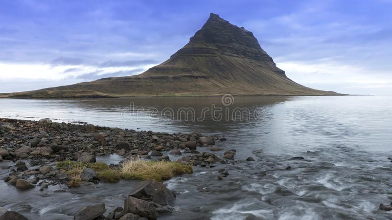 kirkjufell Berg met een meer in voorgrond en blauwe bewolkte hemel royalty-vrije stock fotografie