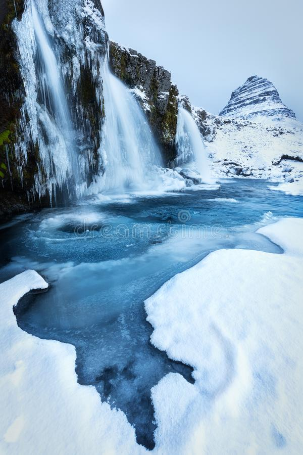 Kirkjufell in blue. Freezing winter day at Iceland`s most recognizable landmarks - the mighty mountain Kirkjufell royalty free stock photography