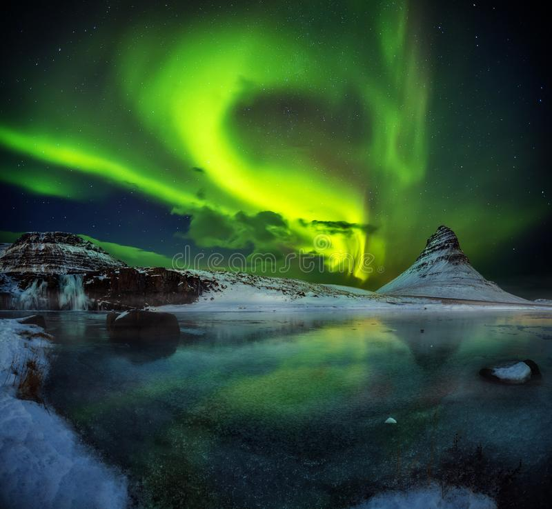 Kirkjufell mountain with beautiful aurora borealis and frozen wa royalty free stock photo
