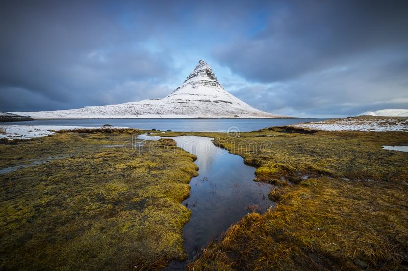 Kirkjufell is one of the most beautiful mountains in Iceland. Snow over kirkjufell in the early morning after a very cold night royalty free stock image