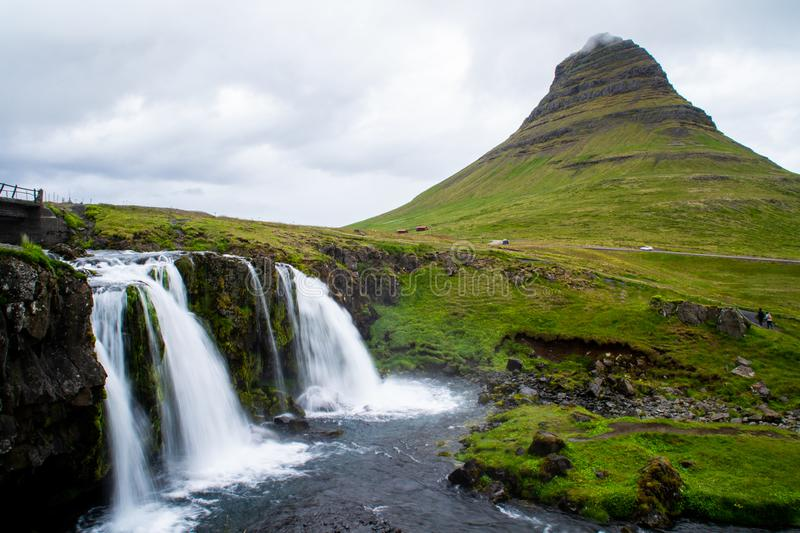 Kirkjufell volcano mountain, long exposure waterfall,  Iceland. Scenic panorama view of long exposure falling water in front of Kirkjufell volcano mountain, the stock images